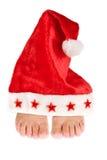 Keeping your feet warm. Two feet keeping warm under a christmas santa hat Royalty Free Stock Photos