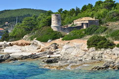 Kefalonia rocks. View from cruise ship on Kefalonia rocky shore and some remains of an old house near Fiskardo port. A girl is suntanning laying on rocks in Stock Images