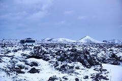 Keflavik - январь 2019: 2 автобуса стоя на дороге в середине красивого исландского ландшафта со снегом покрыли стоковые фото