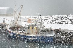 Fishing boat in a snowstorm royalty free stock images