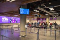 KEFLAVIK, ISLÂNDIA - 15 DE MARÇO DE 2015: Os passageiros do ar do wow que esperam o registro no aeroporto internacional de Keflav fotografia de stock royalty free