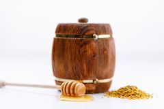 A keg of honey and a wooden spoon with a drop of tasty liquid and a scattering of pollen on a white background. Close-up royalty free stock photos