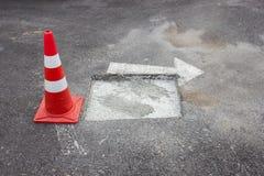 Kegel legte auf die geschädigte Straßenwartereparatur Stockbild