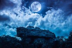 Kei tegen blauwe hemel met wolken en mooie volle maan bij stock afbeeldingen