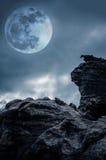 Kei tegen hemel met wolken en mooie volle maan bij nacht royalty-vrije stock foto