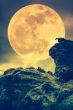 Kei tegen hemel met wolken en mooie volle maan bij nacht royalty-vrije stock afbeeldingen