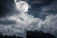 Kei tegen hemel met wolken en mooie volle maan bij nacht stock afbeelding