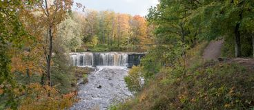 Keila-Joa waterfall and river in golden autumn red and yellow colors. Nice panorama. royalty free stock images