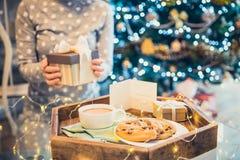 Kein öffnender Präsentkarton junge Frau des Gesichtes Weihnachtsmit unscharfem hölzernem Behälter mit festlichem Frühstückskakao  stockfotografie