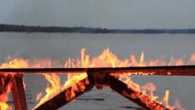 Kein Ton Extremer Nahaufnahmehitzeschleier von einem brennenden Picknicktisch am Ende einer Partei durch einen Gewässer stock footage