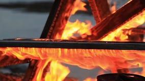 Kein Ton Extremes Nahaufnahmevideo eines brennenden Picknicktischs am Ende einer Partei durch einen Gew?sser stock video footage