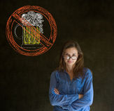 Keine Bieralkoholfrau bewaffnet gefaltet, Sie auf Tafelhintergrund betrachtend Stockbilder