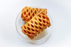 Kekse angefüllt mit rotem Stau auf einer transparenten Glasplatte auf einem weißen Hintergrund lizenzfreie stockfotos