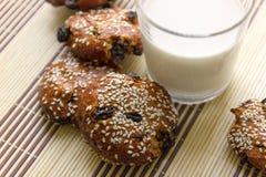 Kekse auf dem Tisch mit Samen des indischen Sesams, Rosinen und einem Glas Milch Stockfotografie