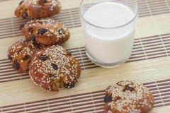 Kekse auf dem Tisch mit Samen des indischen Sesams, Rosinen und einem Glas Milch Lizenzfreies Stockfoto