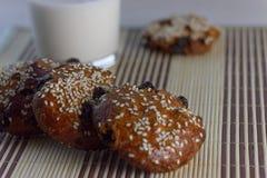 Kekse auf dem Tisch mit Samen des indischen Sesams, Rosinen und einem Glas Milch Lizenzfreie Stockbilder