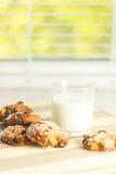 Kekse auf dem Tisch mit Samen des indischen Sesams, Rosinen und einem Glas Milch Auf dem Fensterbrett Gesundes Essen Lizenzfreie Stockfotos
