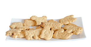 Kekse für Kinder, Tierform, weiße Platte, lokalisiert auf w Lizenzfreie Stockbilder