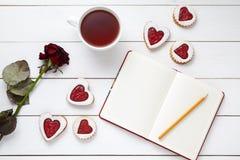 Keksherz formte Plätzchen mit leerem Notizbuch, Bleistift, Tasse Tee und rosafarbener Blume auf weißem hölzernem Hintergrund für Lizenzfreies Stockfoto