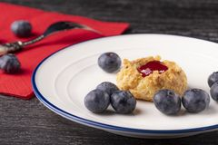 Keksplätzchen gemacht vom Walnussteig mit Erdbeermarmelade auf einer Platte mit Blaubeeren Gabel auf einer roten Serviette stockfotos