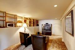 Kelderverdiepingsruimte met TV en twee leerstoelen Stock Foto