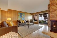 Kelderverdiepingswoonkamer met open haard en stakingsterras Stock Afbeelding