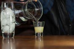 Kellner an auslaufendem Soda des Zählers vom Krug in Glas mit Saft stockfotos