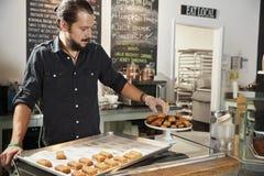 Kellner-Behind Counter In-Kaffeestube, die Plätzchen-Anzeige vereinbart lizenzfreies stockbild
