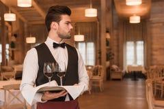 Kellner, der Behälter mit Weingläsern hält Lizenzfreies Stockbild