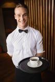 Kellner, der Behälter mit Kaffeetasse hält Lizenzfreies Stockfoto