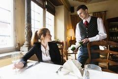 Kellner, der bei Tisch dem weiblichen Kunden Weinflasche im Restaurant zeigt Lizenzfreie Stockbilder