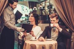 Kellner, der Bestellung von den stilvollen wohlhabenden Paaren entgegennimmt Stockfotografie