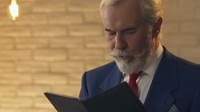 Kellner, der dem alten Mann im Restaurant, Kunde entsetzt durch Kosten, Nahaufnahme Rechnung gibt stock video
