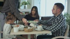 Kellner, der dem kleinen hübschen Mädchen Teigwaren zu Abend isst mit ihrer Familie im Restaurant holt Sie haben Eltern ihr aß stock video footage