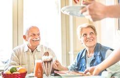 Kellner, der die älteren Paare im Ruhestand essen Kuchen an der Modestange dient stockbild