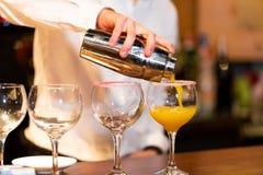 Kellner, der ein Cocktail vorbereitet lizenzfreies stockbild