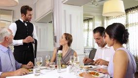 Kellner, der ein Tabelle von lächelnden Freunden beachtet stock video