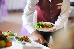 Kellner, der eine Platte trägt Stockfoto