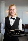Kellner, der einen Behälter mit Kaffeetassen im Restaurant hält Lizenzfreies Stockbild