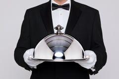 Kellner, der einen silbernen Cloche anhält Stockfoto