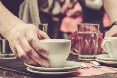Kellner, der einen Tasse Kaffee auf einer Tabelle dient lizenzfreie stockfotografie
