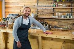 Kellner, der entgegengesetzt mit Serviette im café abwischt lizenzfreie stockbilder