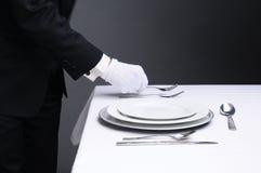 Kellner, der formalen Abendtisch einstellt Stockbild