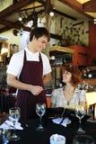 Kellner, der mit costumer an der Gaststätte spricht Stockfotografie