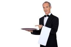 Kellner, der seinen Behälter zeigt Stockfotografie