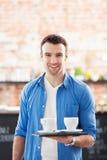 Kellner mit Kaffee auf Behälter Stockbild