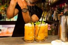Kellner, der zuhause orange Hurrikancocktail vom Nachtklub auf strömendem Spitzenzucker über grünen tadellosen Blättern macht lizenzfreies stockfoto