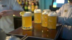 Kellner, der zwei Gläser Bier von der Tabelle nimmt stock footage