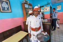 Kellner des populären indischen Cafés im ethnischen Kleid, das im bunten Innenraum arbeitet Stockbild