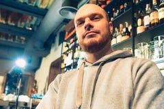 Kellner in einer Kneipe nahe Bierhähnen lizenzfreie stockbilder